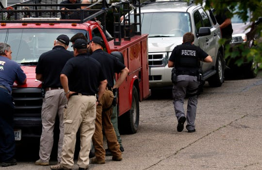Law enforcement officers gather at the hood of a truck being impounded as part of an investigation between the Major Crimes Unit and Drug Enforcement Administration Wednesday morning, Aug. 22, 2018, in Lancaster. MCU, DEA, FBI and Lancaster Police raided a home at 205 S. Cedar Ave. and another building at 128 Welsh Ave. as part of the investigation.