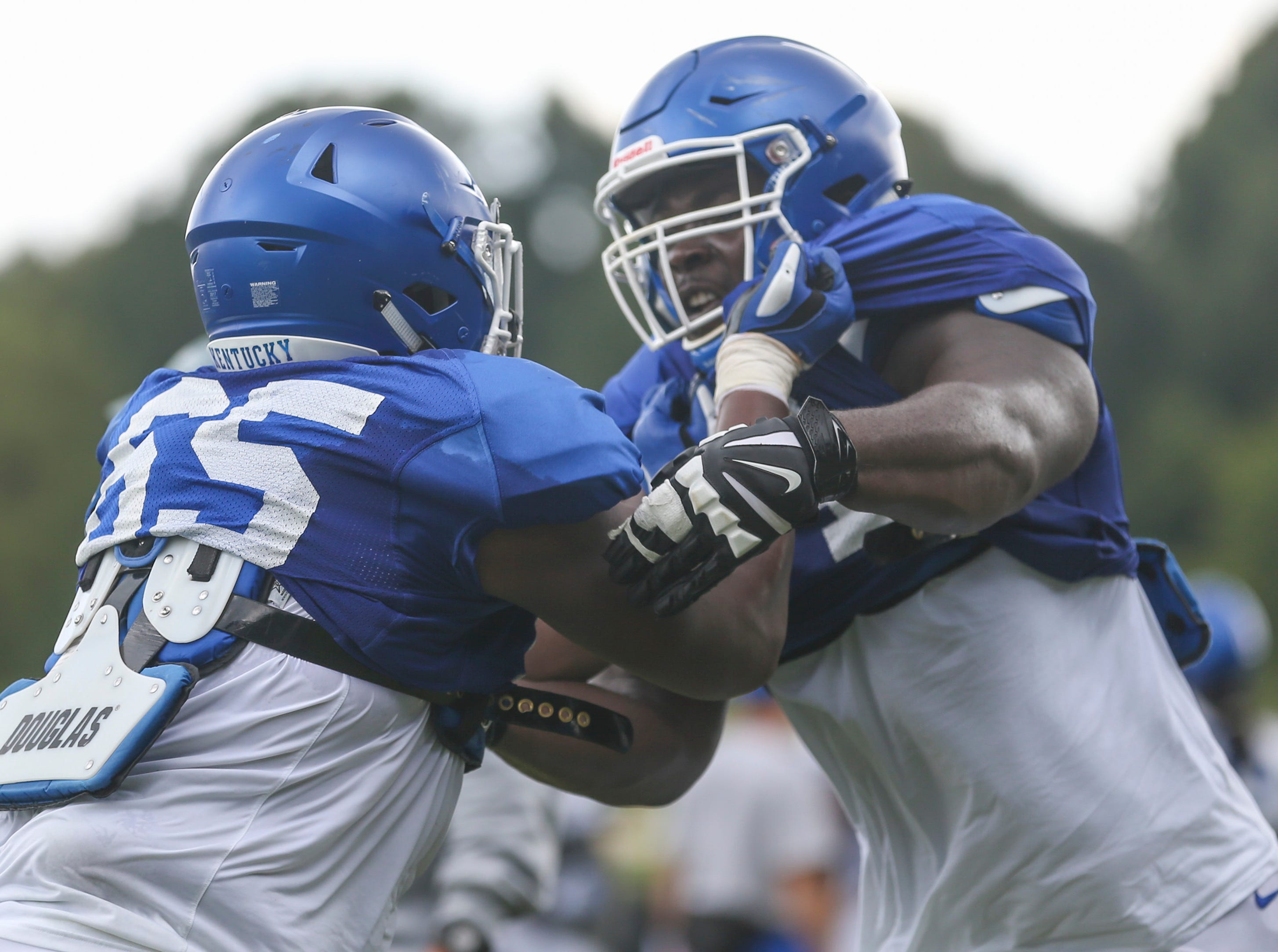 UK offensive guard George Asafo-Ajei, right, pushes back on Bunchy Stallings during a blocking drill at a recent practice. The Wildcats open the season with a home game against Central Michigan Sept. 1 at 3:30 p.m.