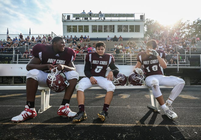 Kiyaunta Goodwin, left, sits with teammates Jaren McDonald, center, and Graham Carnes during a recent Holy Cross football game. Goodwin, 14, already stands at 6 feet 7 inches and has received college football scholarship offers.