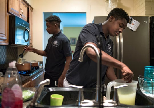 Twin brothers Kimani, left, and Kemar Williams, 15, prepare dinner Monday evening, Aug. 20, 2018.  They live at their grandmother's home on Lansing's southside.