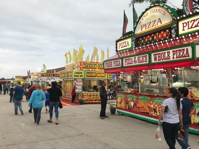 Vendors light up their stalls as the Manitowoc County Fair opens Tuesday night.