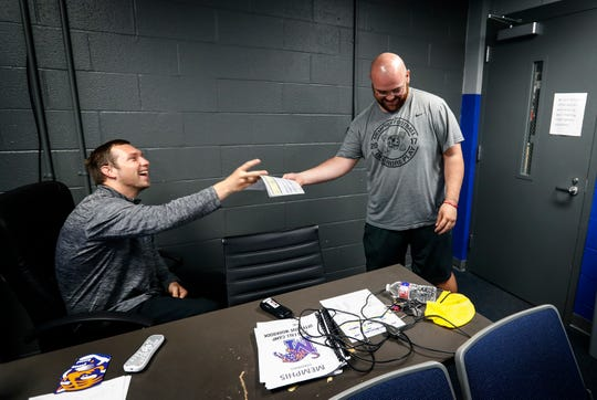 University of Memphis first-time offensive coordinator Kenny Dillingham (left) gets a copy of sequence of plays for practice from Cooper Williams the offensive analysts. At 28-years-old, Dillingham is one of the youngest offensive coordinators in college football.