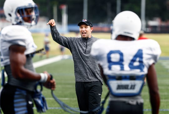 University of Memphis first-time offensive coordinator Kenny Dillingham chats with players during a recent practice. At 28-years-old, Dillingham is one of the youngest offensive coordinators in college football.