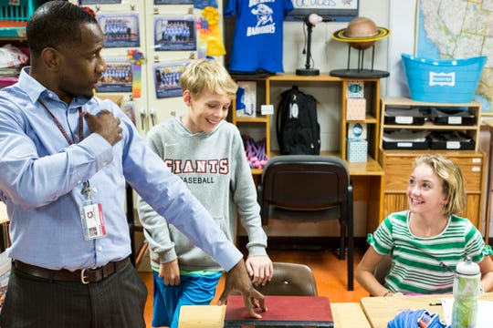 Instructional coach Carlos Saulsberry gets smiles from Preston Johns, 10, center, and Georgia Heart, 10, right, while working in the fifth grade class at Dogwood Elementary in Germantown.