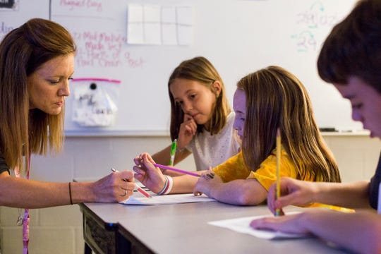 Aug. 22, 2018 - Instructional coach Jennifer Ledford, left, helps Emily Turner, 9, with work in the fourth-grade class at Dogwood Elementary in Germantown. The Germantown Municipal School District's recently amended transfer policy will address overcrowding at district elementary and middle schools.