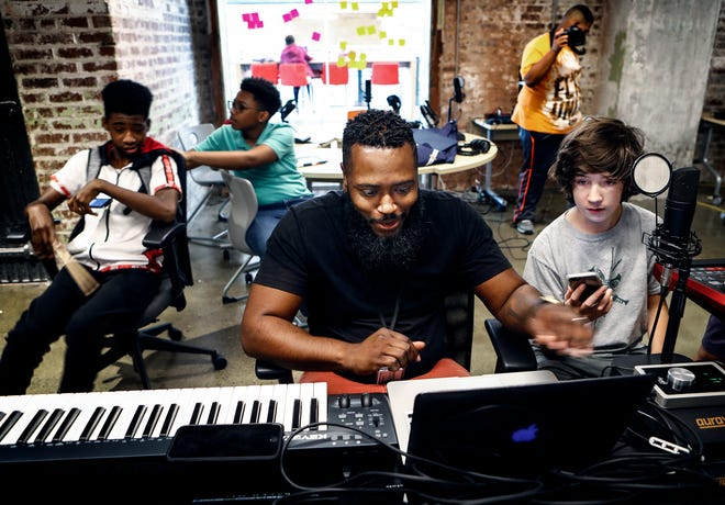 Ty Boyland (middle) with Memphis Music Initiative, works with 9th-grader Richard Baldwin (right) during a music production exploration session at Crosstown High School. The high school works with community partners to offer real-world knowledge that helps students develop skills and experiences.