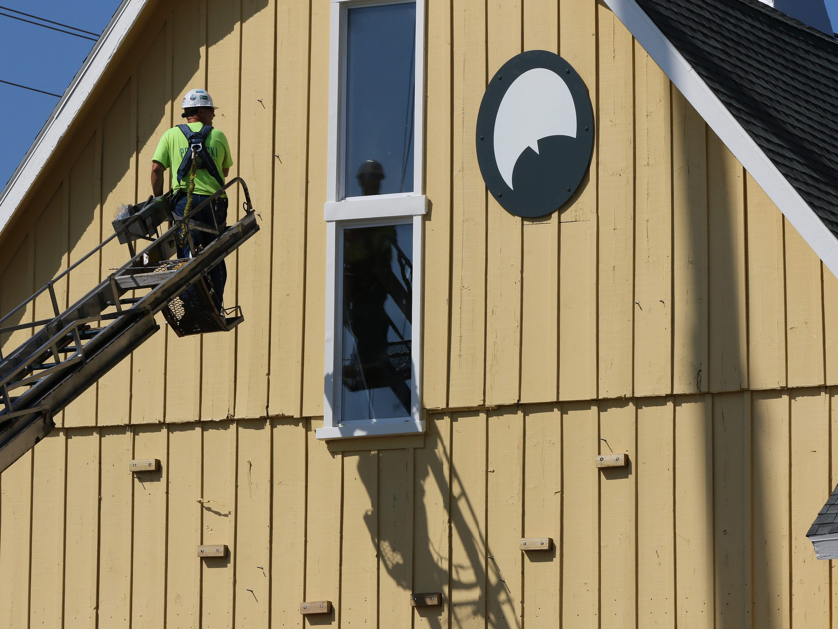 Mike Rutkowski of Poblocki Sign Co. repositions the lift to install a second eye to the east side of The Barn in Delafield on Aug. 22.