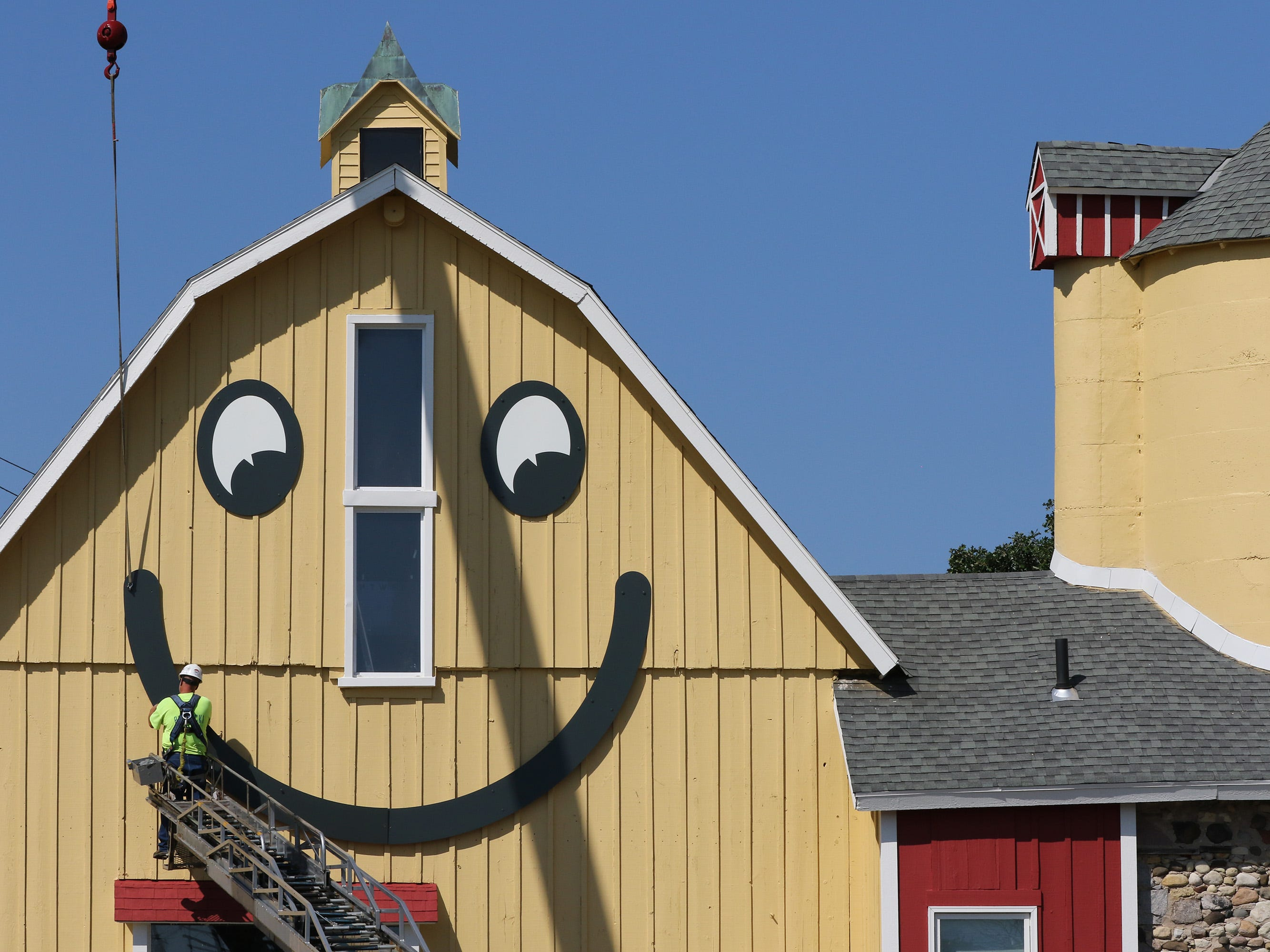 Mike Rutkowski of Poblocki Sign Co. makes that last connections to the smile on the east side of The Smiley Barn in Delafield on Aug. 22.