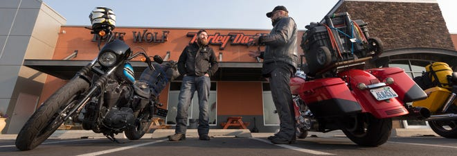 Early birds Ian Andersen (left) and Jay Coy chat while waiting for others to show up for the day's ride Wednesday at Lone Wolf Harley-Davidson in Spokane Valley, Washington.