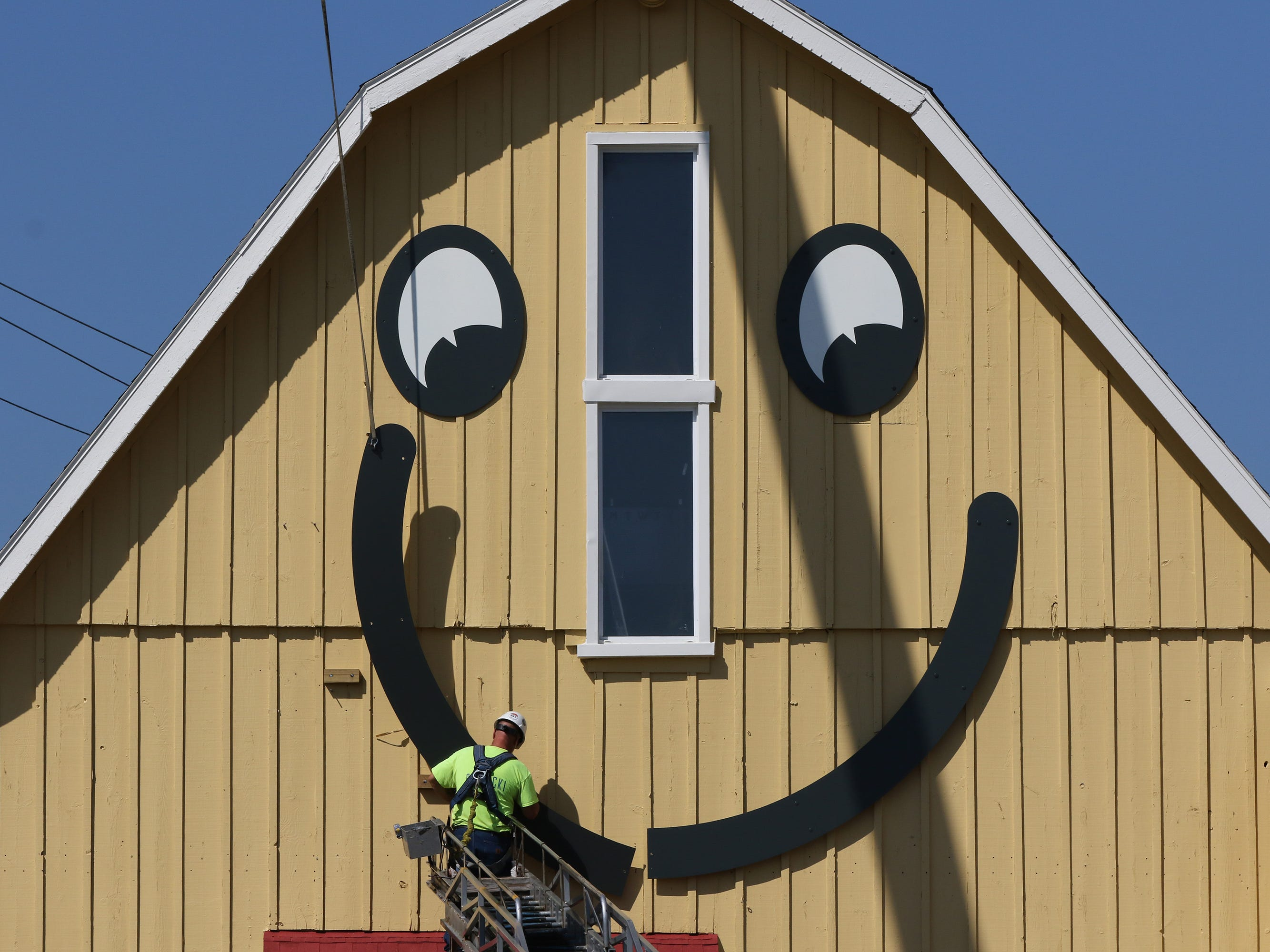 Mike Rutkowski of Poblocki Sign Co. installs one of two parts of the smile to the east side of The Barn in Delafield on Aug. 22.