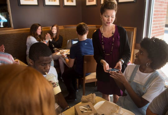 Booker T. Washington art teacher Rachel Dudley looks through photographs of artwork with student Alanna Johnson at a Panera Bread restaurant in Montgomery, Ala., on Wednesday, Aug. 22, 2018. The students lost most of their work in a Saturday morning fire but do have photographs saved.