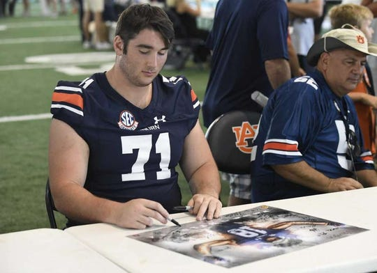 Auburn right tackle Jack Driscoll signs a poster during Fan Day on Saturday, Aug. 11, 2018.