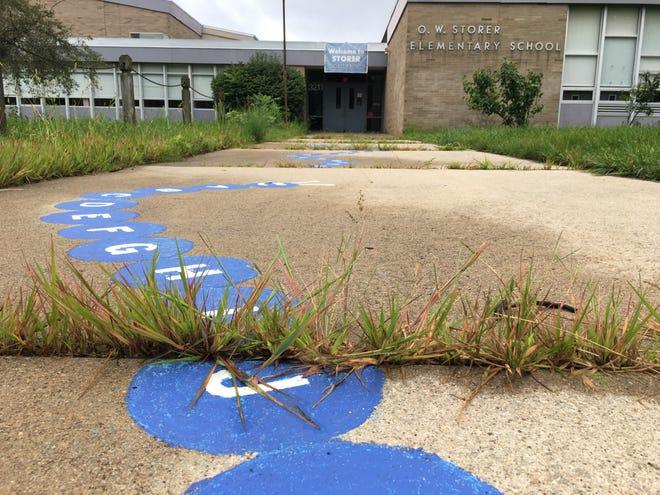 Weeds sprout through cracks in the sidewalk at Storer Elementary School.