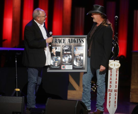Mike Dungan, chairman and CEO of Universal Music Group Nashville presents a plaque to Trace Adkins at the Grand Ole Opry Tuesday August 21, 2018.