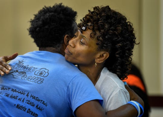 Shaundelle Brooks, mother of Akilah Dasilva, left hugs Shirl Baker, mother of DeEbony Groves, during the mental health hearing of suspect Travis Reinking in criminal court Wednesday, Aug. 22, 2018, in Nashville, Tenn. Reinking is suspected of killing four people in a mass shooting in April at a Nashville Waffle House.