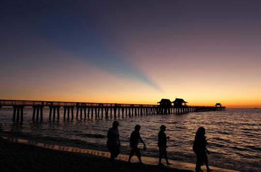 "Beachgoers walk along the Gulf shore near the Naples Pier at sunset. Naples annually makes many national ""best"" lists."