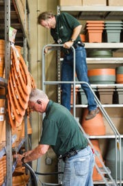 Pete Berkowitz tags some items as Darrell Beckham steps off a ladder in the outdoor section of Orchard Supply Hardware's new store in Naples on Feb. 27, 2017. Orchard Supply Hardware, an American retailer of home improvement and gardening products with two locations in the Naples area, is closing all its stores.