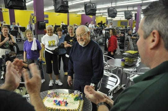 "Francis Smith, 102, celebrates at Planet Fitness, where he works out three times a week. His wife Priscilla is to the left in the ""PF"" shirt.  Photo by Lance Shearer"