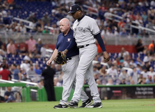 New York Yankees relief pitcher Aroldis Chapman, right, leaves the game with an injury during the twelfth inning of a baseball game against the Miami Marlins, Tuesday, Aug. 21, 2018, in Miami. The Yankees won 2-1 in 12 innings.