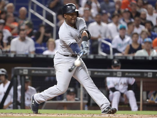 New York Yankees' Miguel Andujar hits a single during the fourth inning of a baseball game against the Miami Marlins, Tuesday, Aug. 21, 2018, in Miami.