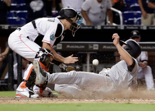 New York Yankees' Kyle Higashioka, right, scores the go-ahead and eventual game-winning run on a sacrifice fly by Miguel Andujar as Miami Marlins catcher J.T. Realmuto waits for the throw during the 12th inning of a baseball game, Tuesday, Aug. 21, 2018, in Miami. The Yankees won 2-1 in 12 innings.