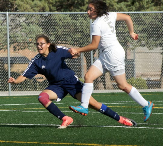 Lady 'Cat sophomore Alissa Cordova (left) keeps an eye on her shot as it found the back of the Chaparral net to give Deming a 2-0 cushion.