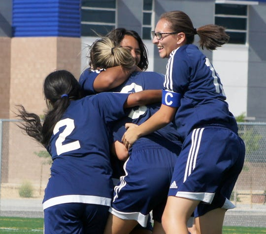 Lady 'Cat teammates mob junior striker Julissa Chavez after she scored Deming's first goal of the season.