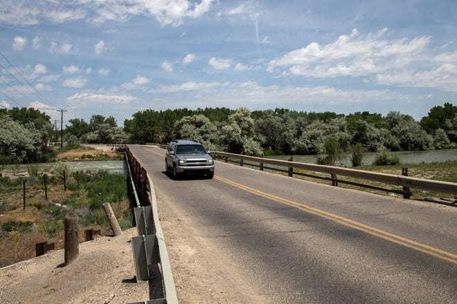 A vehicle crosses over the San Juan River June 11, 2017, on County Road 5500 southwest of Bloomfield.