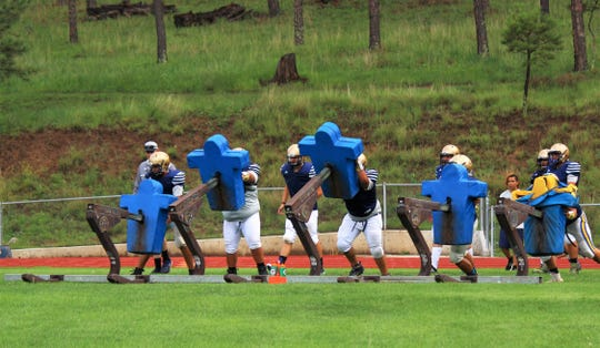 Warriors tackle line-up throws strength and concentration into their moves during a practice. The team will play the first game of the season Aug. 24.