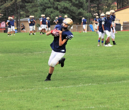 Warrior's receiver completes the catch running the ball down the filed at practices.