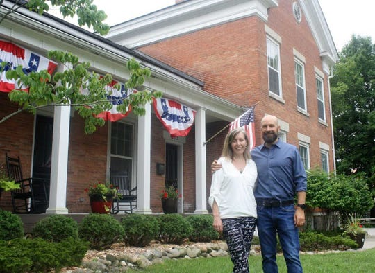 Elizabeth and Rhett Reader stand proudly in front of the historic home they transformed into a sober-living home for recovering drug addicts just south of downtown Milford.