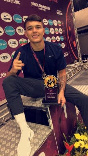 Anthony Mantanona sits with a gold medal around his neck and a trophy  in his hand after winning the Junior Pan-American Championships for wrestling on Sunday.