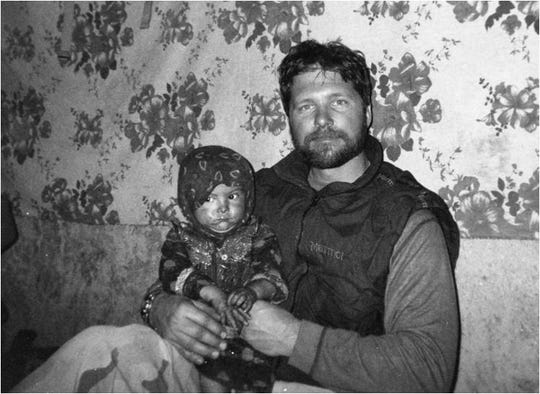 Special Tactics Combat Controller Tech. Sgt. John Chapman holds a young child in Afghanistan in early 2002. President Donald Trump posthumously awarded the Medal of Honor to Chapman's family at a ceremony Wednesday for his heroism in March 2002 while deployed to Afghanistan.