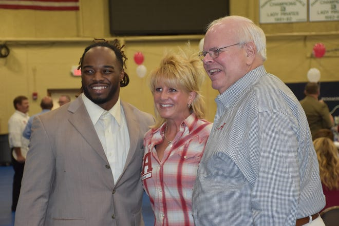 Alabama supporter Nicole Bowen joins with Trent Richardson and famed Crimson Tide broadcaster Eli Gold during Tuesday night's Pensacola Bama Club's annual scholarship kickoff event at Pensacola State College's Hartsell Arena.