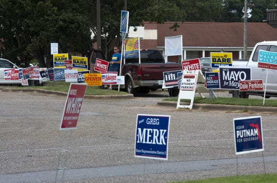 Campaign signs dot the landscape outside an early voting location at Pensacola State College on Wednesday, Aug. 22, 2018.