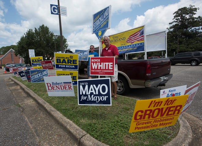District 4 County Commission candidates Terry Strickland and Boyce White spend time campaigning outside an early voting location at Pensacola State College on Wednesday, Aug. 22, 2018.