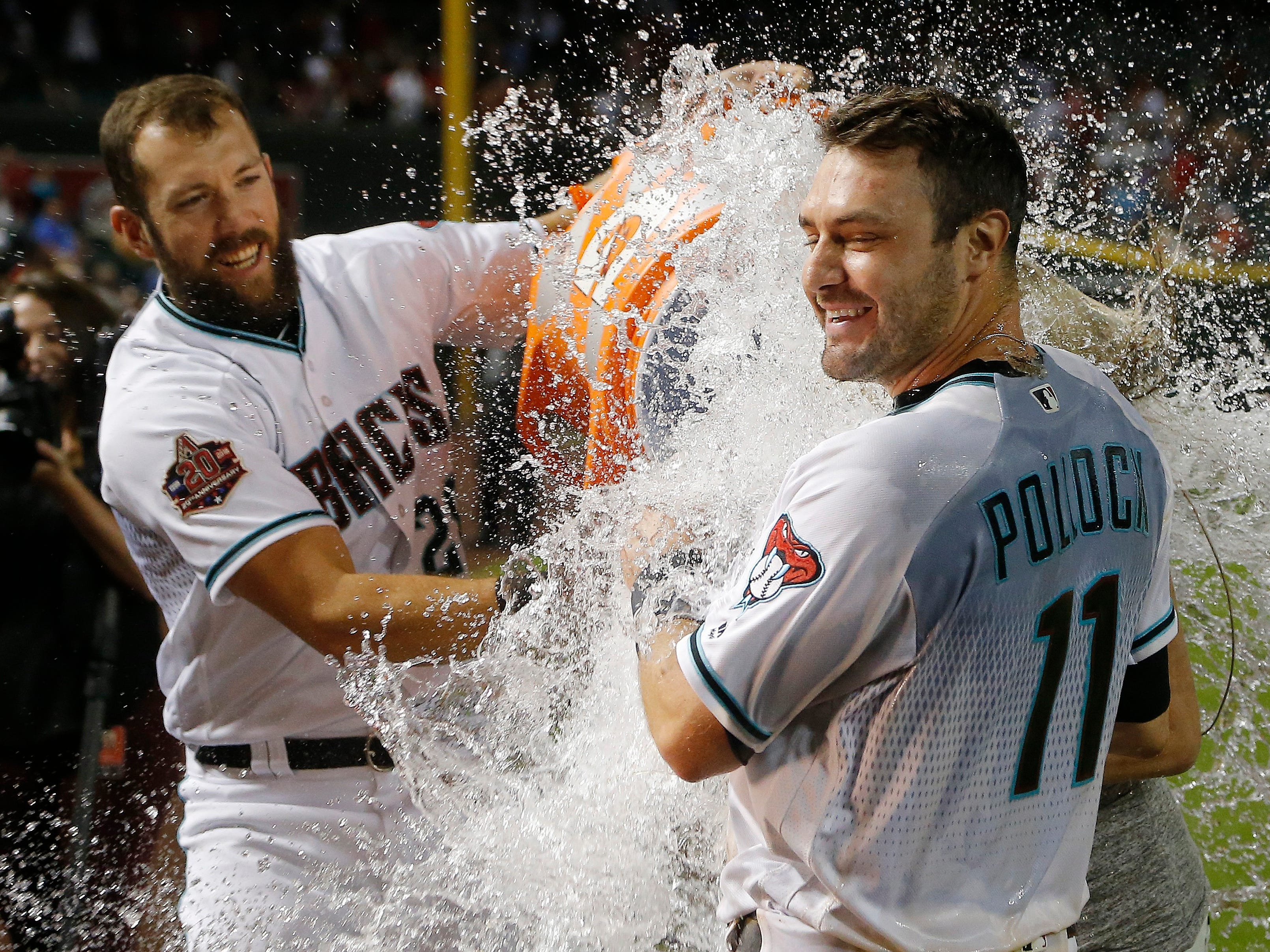 After putting down a sacrifice bunt in the ninth inning, Arizona Diamondbacks' A.J. Pollock (11) gets doused with water by teammate Steven Souza Jr., left, after a baseball game against the Los Angeles Angels, Tuesday, Aug. 21, 2018, in Phoenix. The Diamondbacks defeated the Angels 5-4.