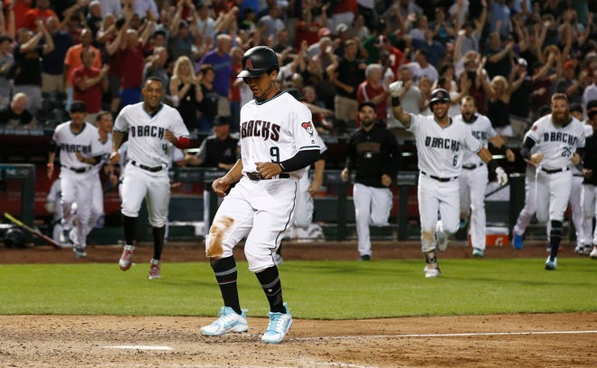 Arizona Diamondbacks' Jon Jay (9) scores the winning run on a throwing error by Los Angeles Angels relief pitcher Cam Bedrosian during the ninth inning of a baseball game, Tuesday, Aug. 21, 2018, in Phoenix. The Diamondbacks defeated the Angels 5-4.