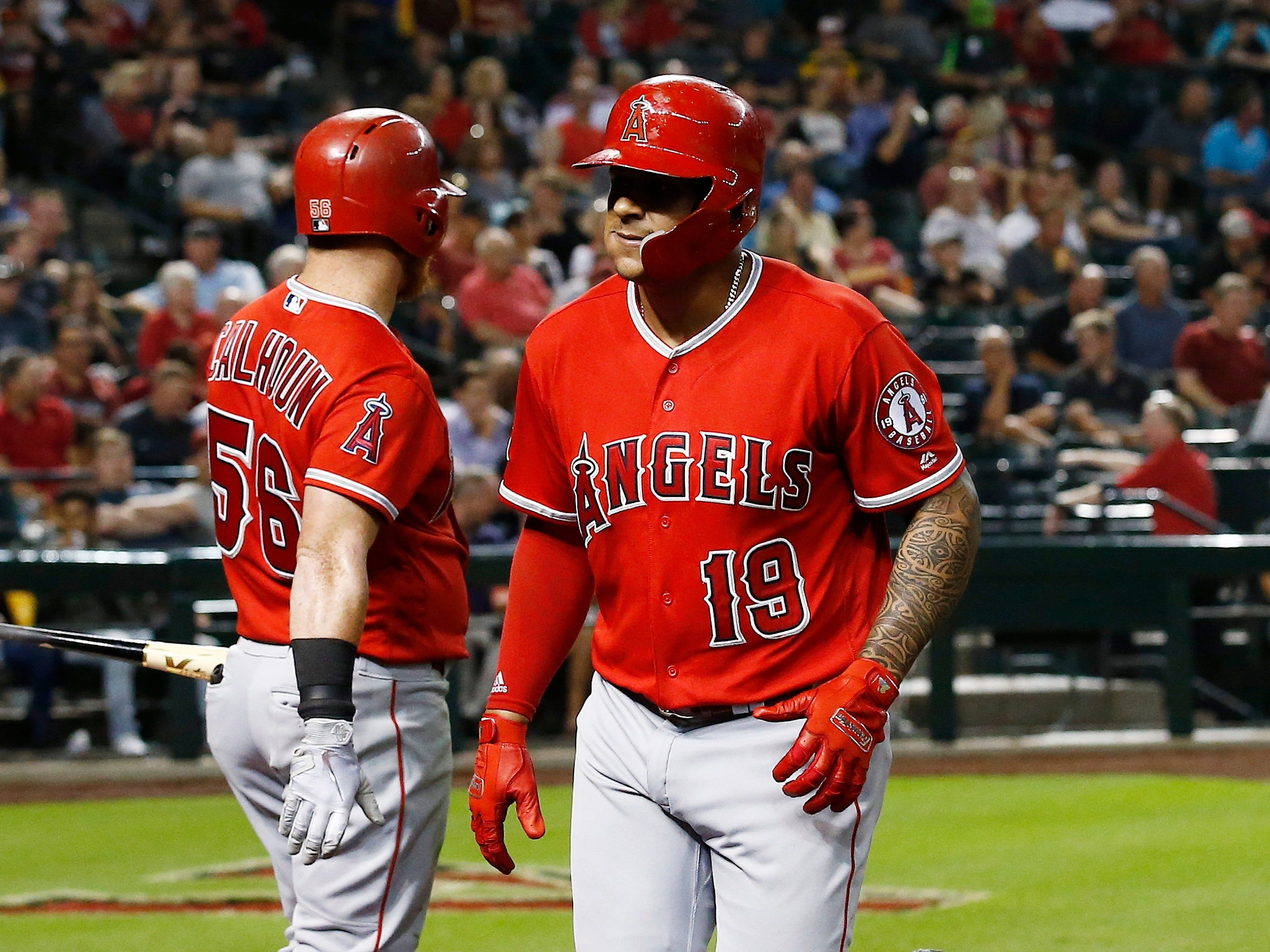 Los Angeles Angels' Jefry Marte (19) heads back to the dugout after celebrating his home run against the Arizona Diamondbacks with Kole Calhoun (56) during the seventh inning of a baseball game Tuesday, Aug. 21, 2018, in Phoenix.