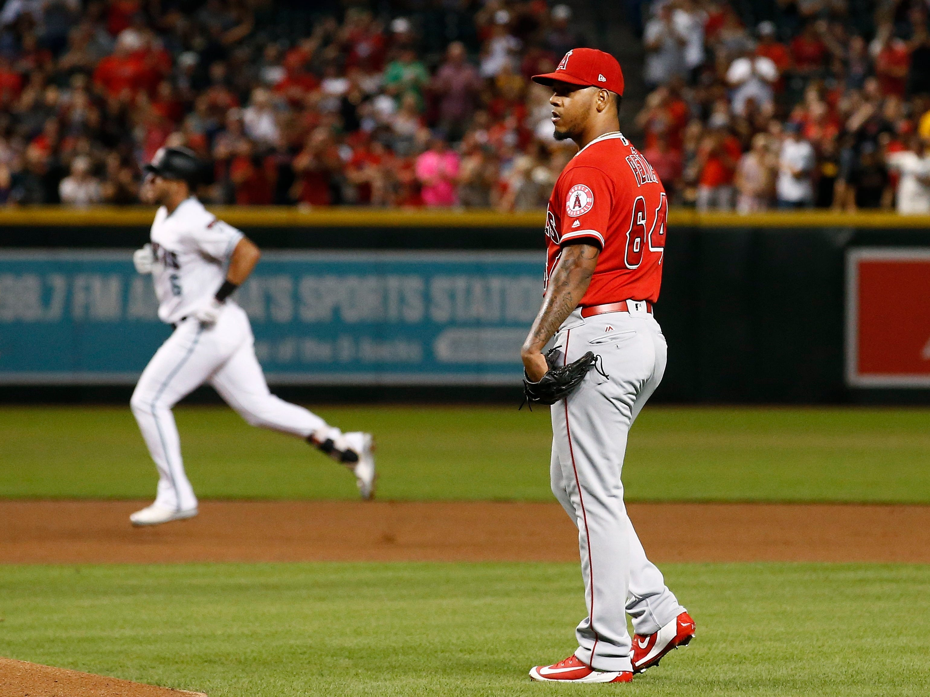 Los Angeles Angels pitcher Felix Pena, right, waits for a new baseball after giving up a two-run home run to Arizona Diamondbacks' David Peralta, left, during the first inning of a baseball game, Tuesday, Aug. 21, 2018, in Phoenix.