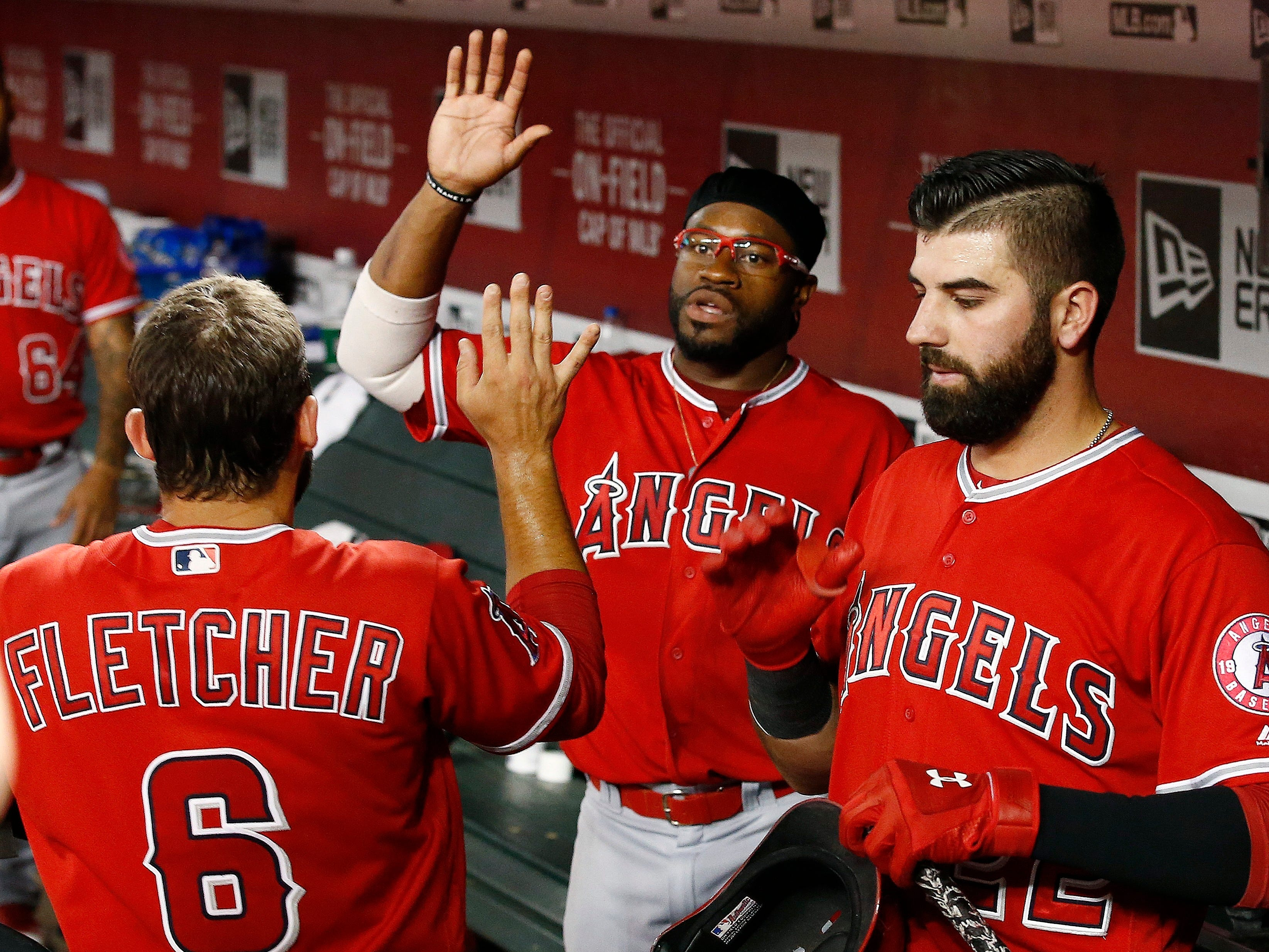 Los Angeles Angels' David Fletcher (6) celebrates his run scored against the Arizona Diamondbacks with Kaleb Cowart, right, and Eric Young Jr., middle, during the third inning of a baseball game Tuesday, Aug. 21, 2018, in Phoenix.