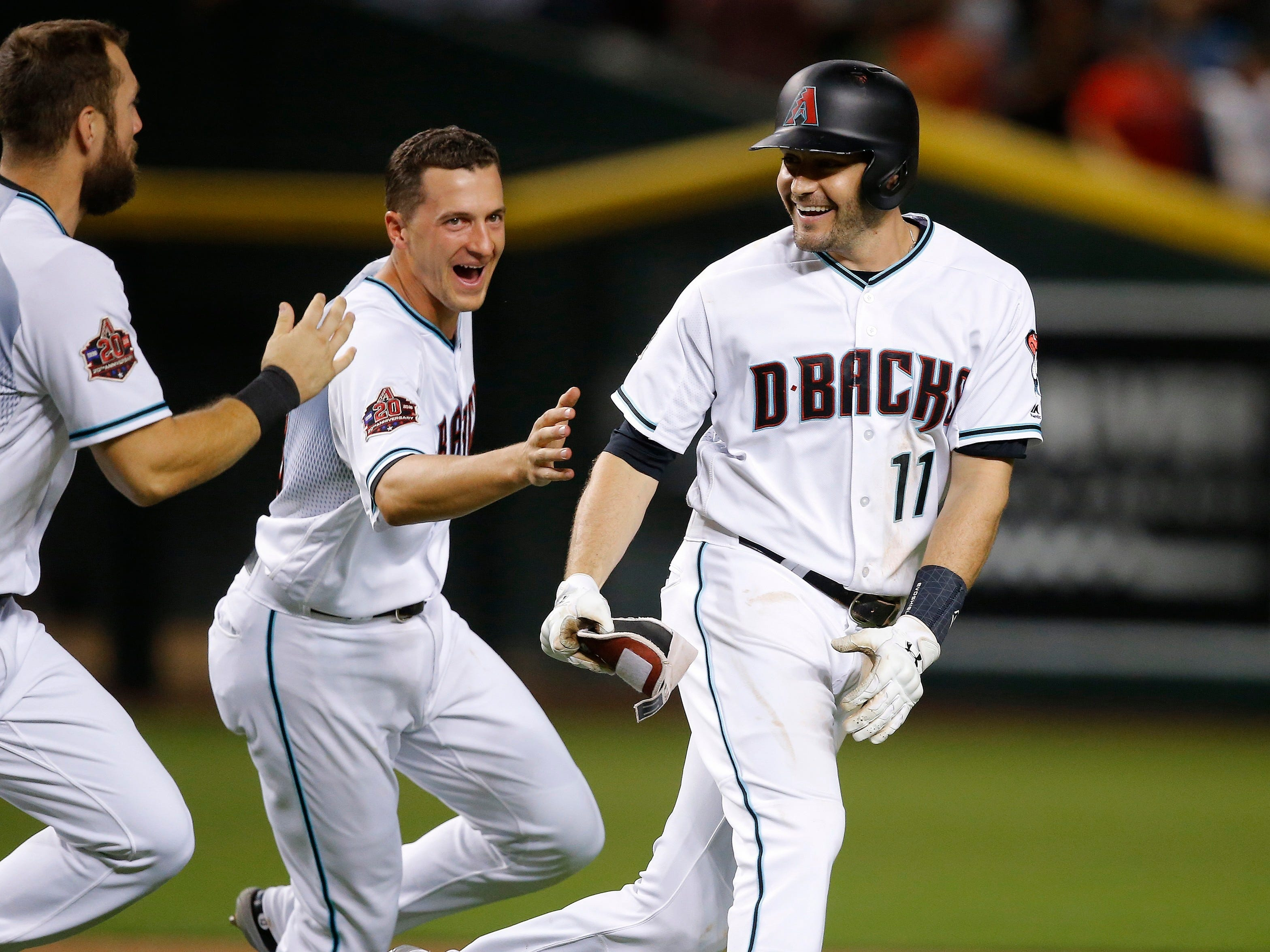 Arizona Diamondbacks' A.J. Pollock (11) celebrates a win against the Los Angeles Angels with Steven Souza Jr., left, and Nick Ahmed, middle, after a baseball game, Tuesday, Aug. 21, 2018, in Phoenix. The Diamondbacks defeated the Angels 5-4.