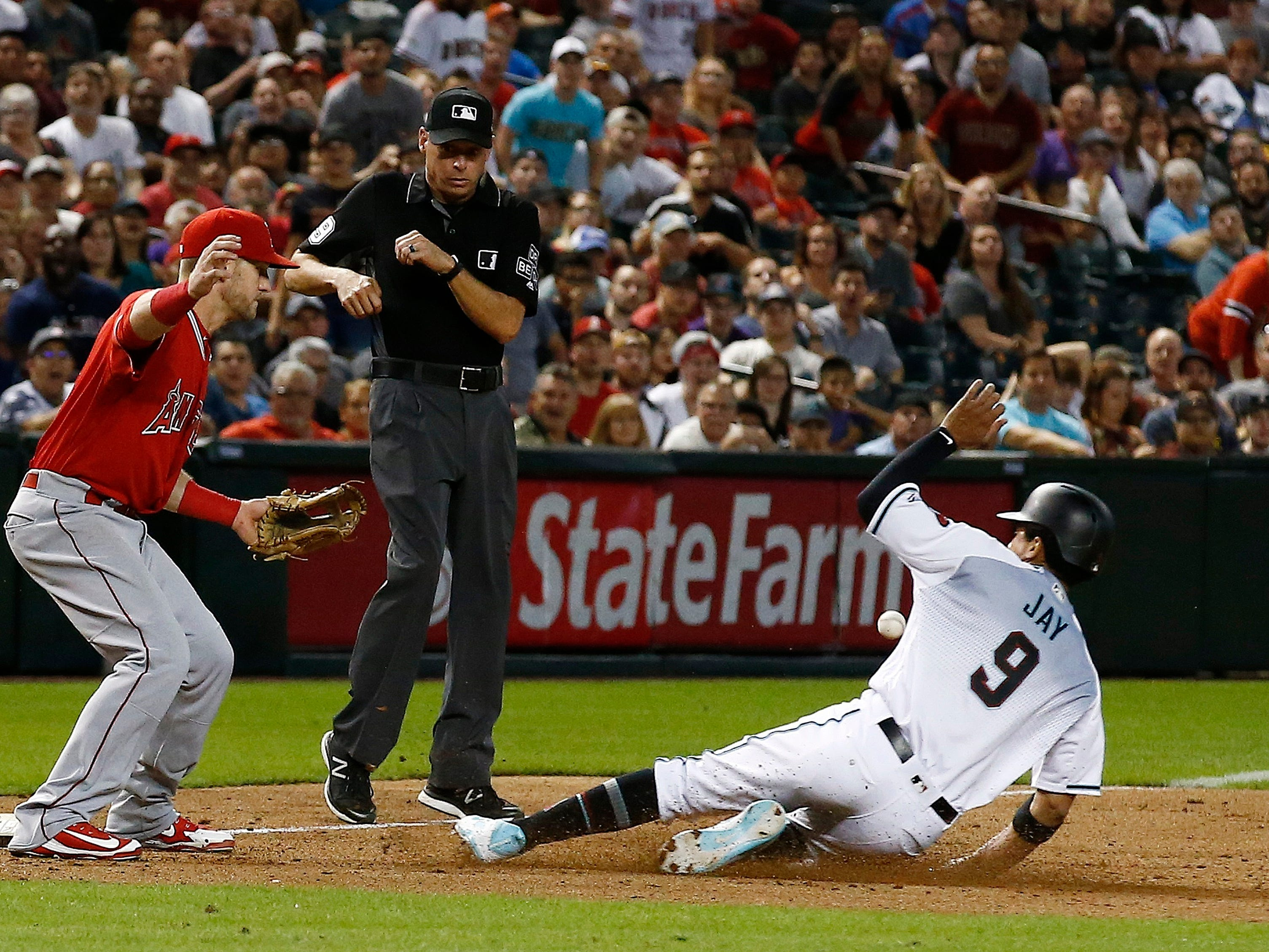 A wild throw by Los Angeles Angels relief pitcher Cam Bedrosian gets past Angels third baseman Taylor Ward, left, as Arizona Diamondbacks center fielder Jon Jay (9) slides safely into third base as umpire Andy Fletcher, middle, looks on during the ninth inning of a baseball game, Tuesday, Aug. 21, 2018, in Phoenix. The Diamondbacks defeated the Angels 5-4.
