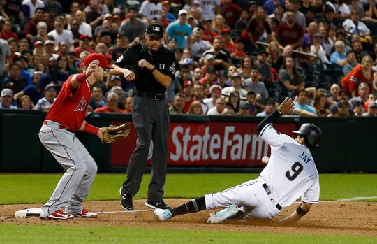 A wild throw by Angels reliever Cam Bedrosian gets past third baseman Taylor Ward (left) as Diamondbacks baserunner Joy Jay slides safely into third base in the ninth inning on Tuesday.