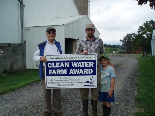 Franklin County Conservation District Board Member Sam Worley presents Justin Geisinger of Air Hill Acres Farm with the Clean Water Farm Award.