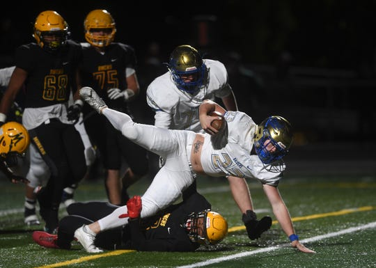 Reed's Champ Robertson (23) falls into the end zone for a touchdown against Bishop Manogue during their football game in Reno on Sept. 22, 2017.