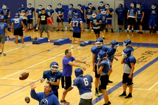 The McNary football team practices inside as wildfire smoke lingers over the Willamette Valley at McNary High School in Keizer on Wednesday, Aug. 22, 2018.
