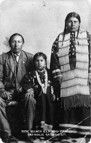 Nicholas Black Elk, left, with daughter Lucy Black Elk and wife, Anna Brings White, photographed in their home in Manderson, S.D., circa 1910. Black Elk wears a suit, his wife wears a long dress decorated with elk's teeth and a hair pipe necklace.