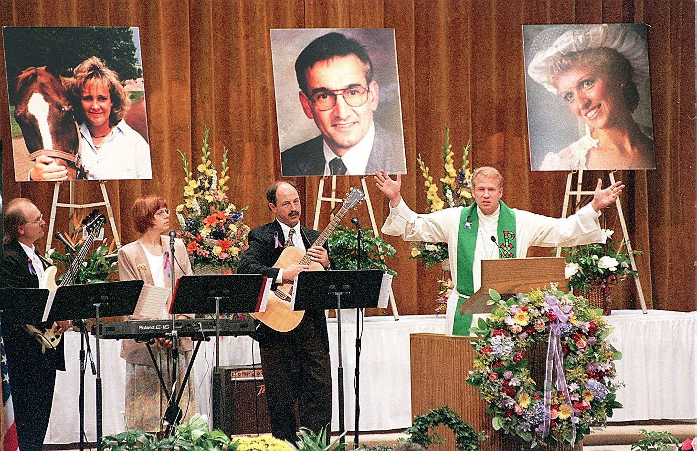 Pastor Brian Mortenson speaks  during a memorial service for three Sioux Valley Hospital workers who perished in a helicopter crash. Photographs of those who died - Shannon Nolte, Merton Tiffany and Melissa Wittry - are shown behind Mortenson.