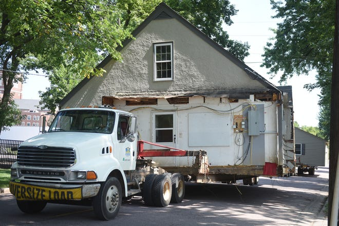 D&C Movers move homes while police escort the homes from Elmwood for a LifeScape proposed parking lot Wednesday, Aug 22, in Sioux Falls. Homes on the block are getting lifted up and shipped elsewhere on trucks.